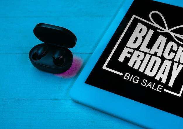 Bovenaanzicht van set gadgets in paars neonlicht, blauwe achtergrond. draadloze oortelefoons, tablet. tech, modern, gadgets, advertentie. zwarte vrijdag, cyber maandag, verkoop, financiën, online aankopen concept.