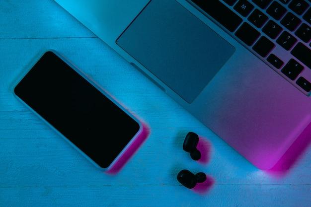 Bovenaanzicht van set gadgets in paars neonlicht en blauw