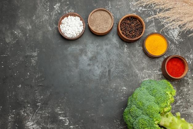 Bovenaanzicht van set van verschillende kruiden in bruine kommen en verse groenten grijze tafel