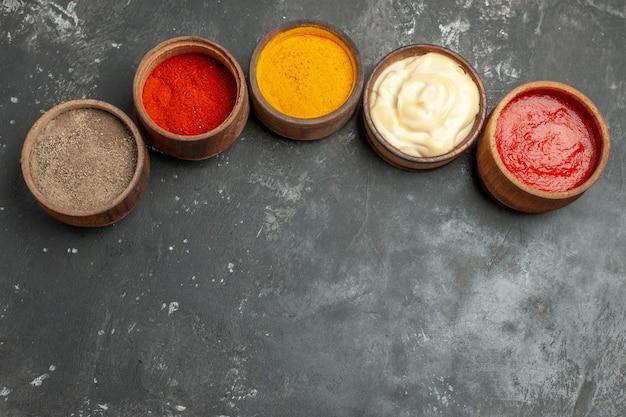 Bovenaanzicht van set voor sauzen met verschillende kruidenmayonaise en ketchup op grijze tafel