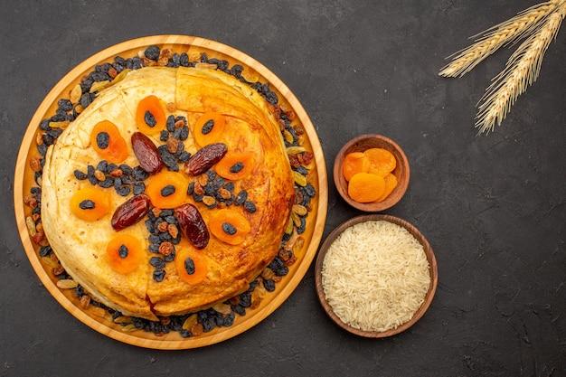 Bovenaanzicht van shakh plov heerlijke rijstmaaltijd gekookt binnen rond deeg met rozijnen op donkergrijs oppervlak