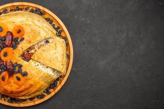 Bovenaanzicht van shakh plov heerlijke rijstmaaltijd gekookt binnen rond deeg met rozijnen op het grijze oppervlak