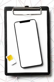 Bovenaanzicht van simkaart met smartphone en klembord