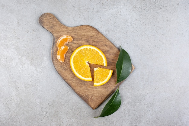 Bovenaanzicht van sinaasappel- en mandarijnplakken op houten snijplank.
