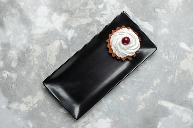 Bovenaanzicht van slagroomtaart met fruit in zwarte cakevorm op grijs-licht bureau, zoete suiker van het cakekoekje