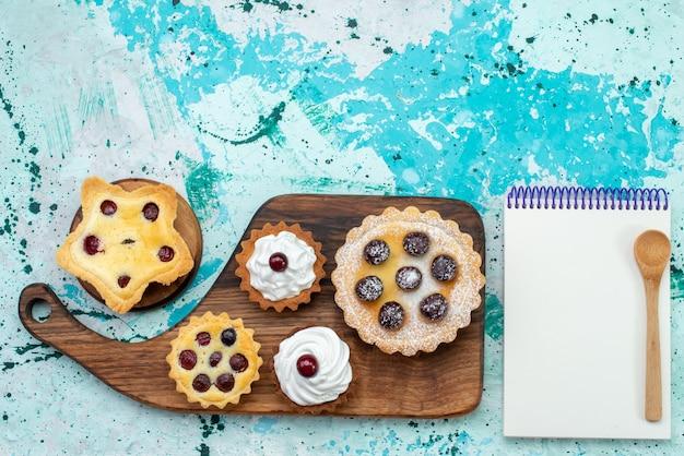 Bovenaanzicht van slagroomtaarten met fruit samen met blocnote op grijs-licht bureau, zoete suiker van het cakekoekje