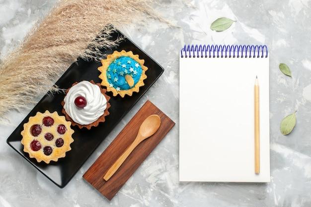 Bovenaanzicht van slagroomtaarten met frutis samen met blocnote op grijs-licht bureau, zoete suiker van het cakekoekje