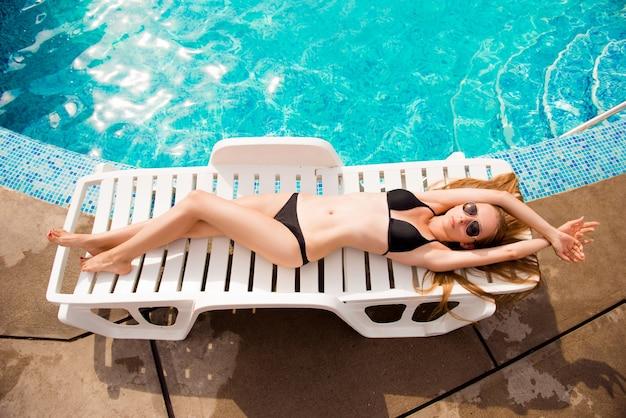 Bovenaanzicht van slank meisje liggend op de zonnebank