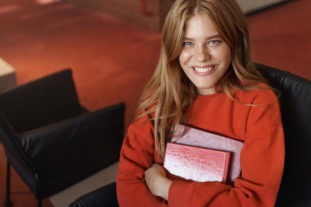 Bovenaanzicht van slimme lachende roodharige meisje zit in bibliotheek en studeren, boeken met stralende grijns blik vast te houden.