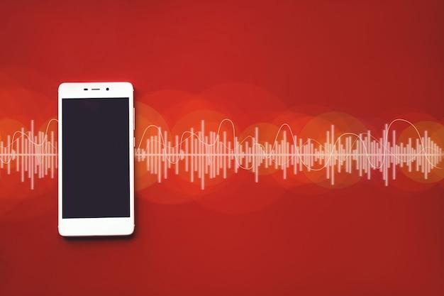 Bovenaanzicht van slimme telefoon tegen rood gekleurde achtergrond met audiotrack. muziekconcept.