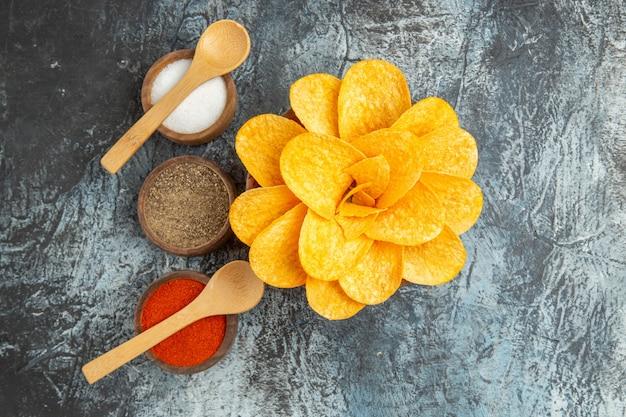 Bovenaanzicht van smakelijke aardappelchips versierd als bloemvormige verschillende kruiden met lepels erop op grijze tafel