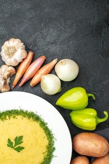Bovenaanzicht van smakelijke aardappelpuree met groenen en verse groenten op zwart