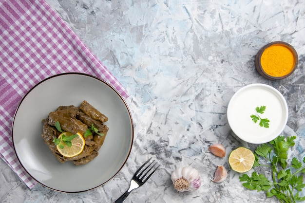 Bovenaanzicht van smakelijke blad dolma met knoflook en yoghurt op witte ondergrond