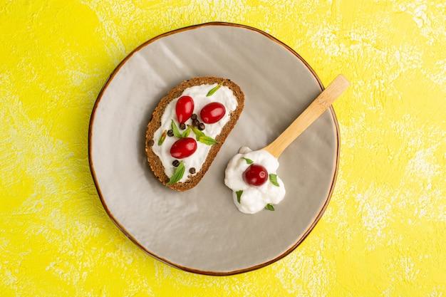 Bovenaanzicht van smakelijke brood toast met zure room en kornoeljes binnen plaat op het gele oppervlak