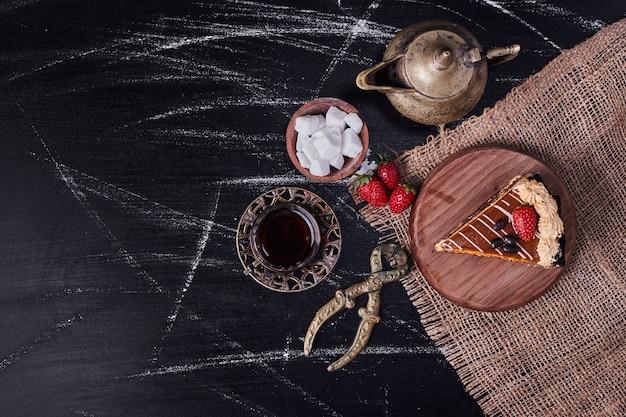 Bovenaanzicht van smakelijke cake omringd door theeservies op marmeren tafel.