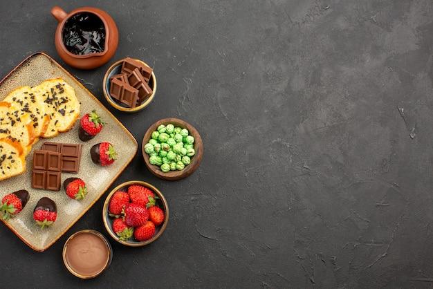Bovenaanzicht van smakelijke cake, smakelijke cake en kommen van chocolade, aardbeien, groene snoepjes en chocoladeroom aan de linkerkant van de tafel