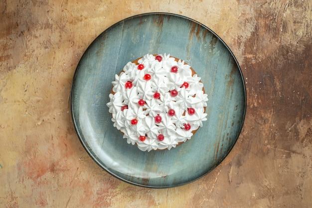 Bovenaanzicht van smakelijke cake versierd met room en bessen op een blauw bord op een kleurrijke achtergrond