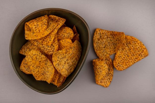 Bovenaanzicht van smakelijke chips op een kom met geïsoleerde chips