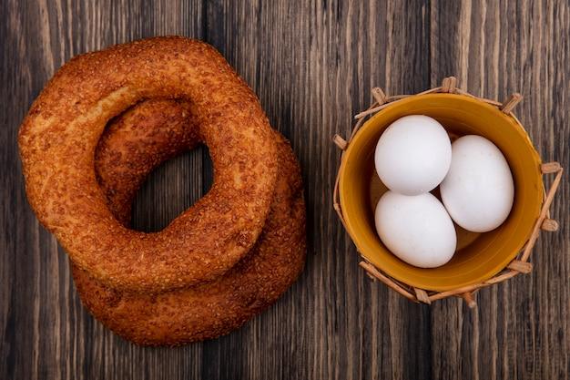 Bovenaanzicht van smakelijke en zachte turkse bagels met eieren op een emmer op een houten achtergrond