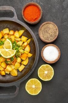 Bovenaanzicht van smakelijke gebakken aardappelen in pan met uien en knoflook rond op het donkere oppervlak