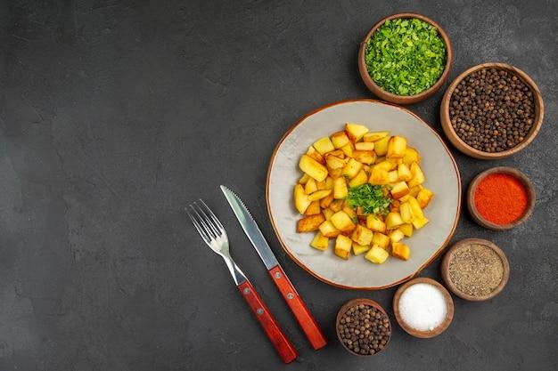 Bovenaanzicht van smakelijke gebakken aardappelen in plaat met groenen en kruiderijen op donkere ondergrond