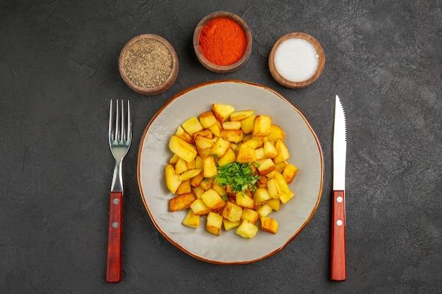 Bovenaanzicht van smakelijke gebakken aardappelen in plaat met kruiden op het donkere oppervlak