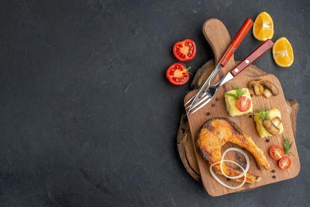 Bovenaanzicht van smakelijke gebakken vis en champignons tomaten groenen op snijplank bestekset peper op zwarte ondergrond