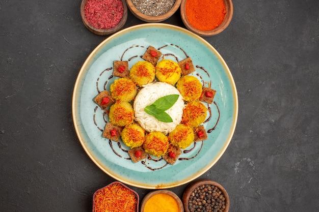 Bovenaanzicht van smakelijke gekookte rijst met gehaktballen en verschillende smaakmakers op dark