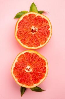 Bovenaanzicht van smakelijke grapefruits fruit plakjes op het roze oppervlak