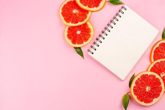 Bovenaanzicht van smakelijke grapefruits met kladblok op roze oppervlak