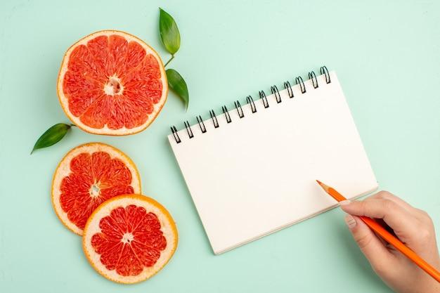 Bovenaanzicht van smakelijke grapefruits, sappig gesneden op het lichtblauwe oppervlak