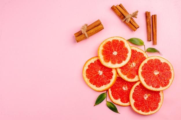 Bovenaanzicht van smakelijke grapefruits sappige fruit plakjes met kaneel op roze oppervlak
