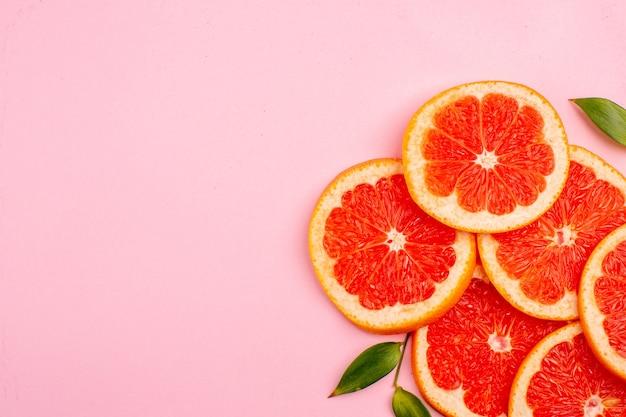 Bovenaanzicht van smakelijke grapefruits sappige fruit plakjes op het roze oppervlak