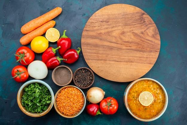 Bovenaanzicht van smakelijke groentesoep met verse groenten groenen en kruiden op donkerblauw oppervlak