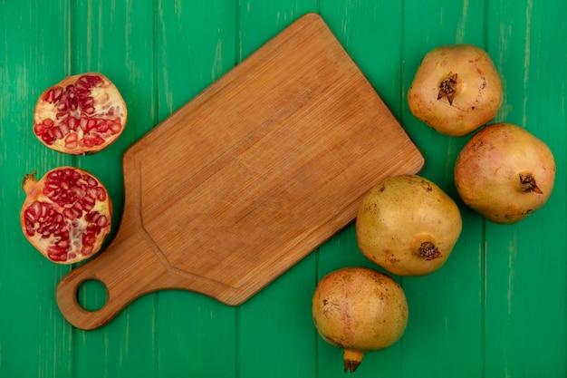 Bovenaanzicht van smakelijke halve en hele granaatappels geïsoleerd op een groene houten muur met kopie ruimte