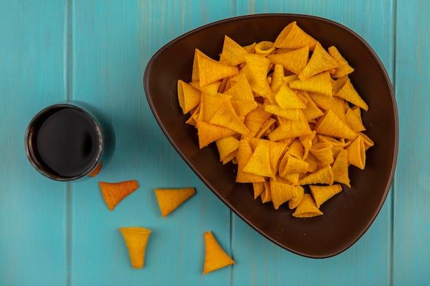 Bovenaanzicht van smakelijke kegelvormige gebakken maïs snacks op een kom met een glas cola