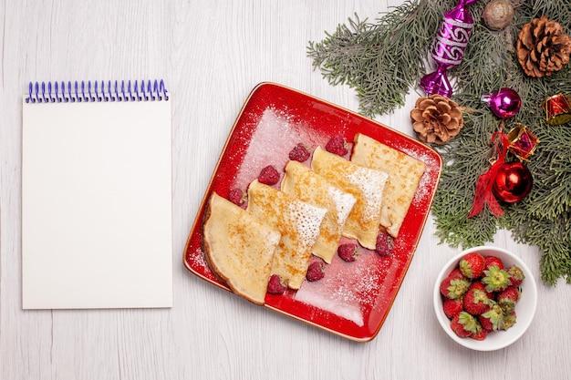 Bovenaanzicht van smakelijke pannenkoeken met fruit op wit