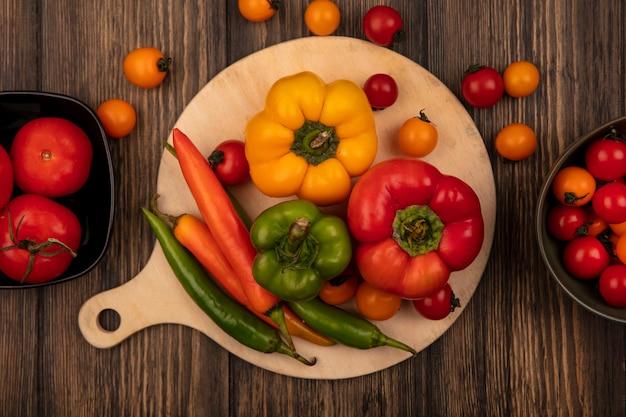 Bovenaanzicht van smakelijke paprika's op een houten keukenbord met verse tomaten op kom op een houten muur