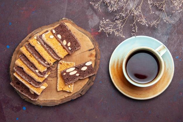 Bovenaanzicht van smakelijke plakjes cake met noten en kopje thee op zwart