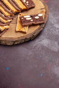 Bovenaanzicht van smakelijke plakjes cake met noten op zwart