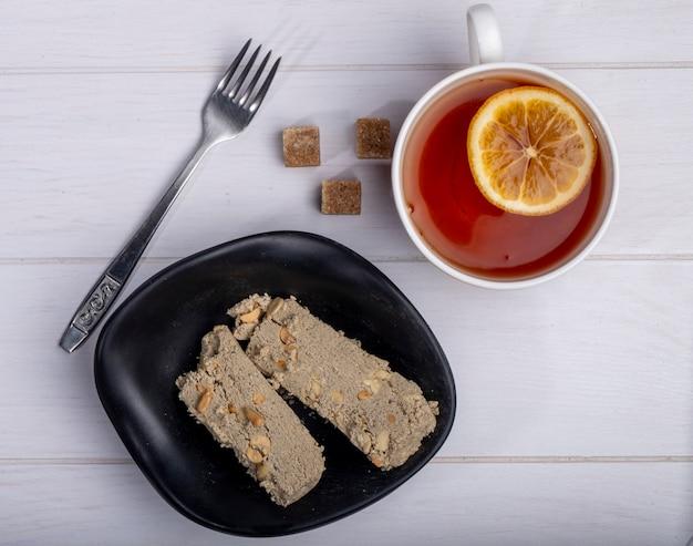 Bovenaanzicht van smakelijke plakjes halva in een bord en een kopje thee met schijfje citroen op wit