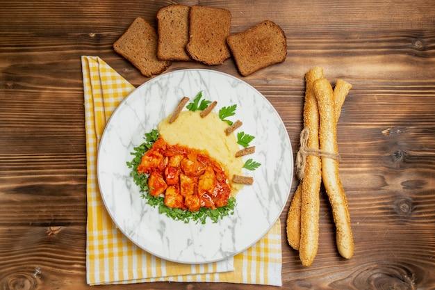 Bovenaanzicht van smakelijke plakjes kip met aardappelpuree en brood op bruine tafel
