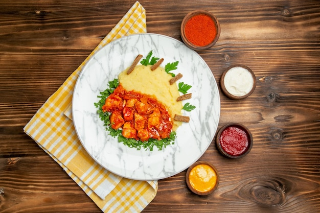 Bovenaanzicht van smakelijke plakjes kip met aardappelpuree en smaakmakers op bruine tafel