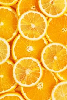 Bovenaanzicht van smakelijke plakjes sinaasappel en citroen. heldere zomer achtergrond. gezond eten. goede voeding. verse sappen. ruimte kopiëren, plat leggen. achtergrondtextuur van vruchten. het concept van citrusvruchtenproducten.