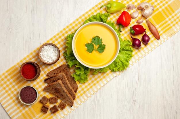Bovenaanzicht van smakelijke pompoensoep met verschillende kruiden en brood op wit