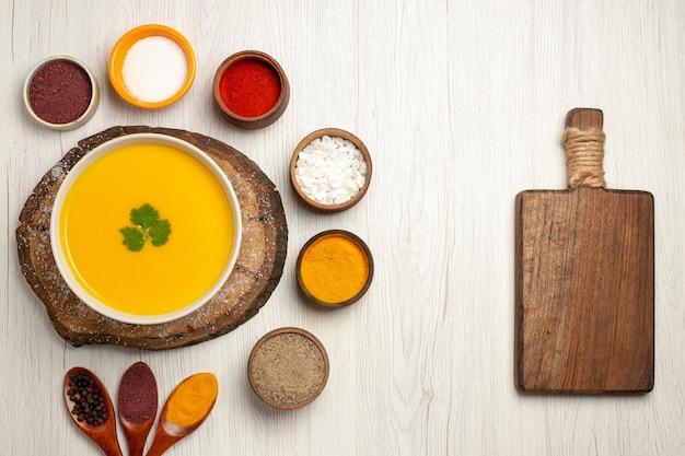 Bovenaanzicht van smakelijke pompoensoep met verschillende smaakmakers op lichtwit