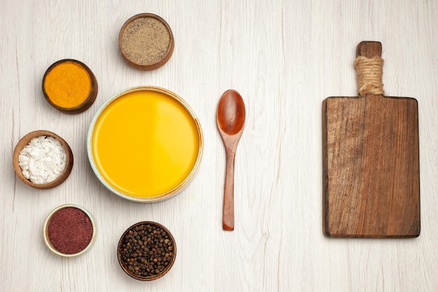 Bovenaanzicht van smakelijke pompoensoepcrème getextureerd met kruiden op witte tafel
