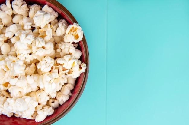 Bovenaanzicht van smakelijke popcorn op een houten kom op blauwe ondergrond