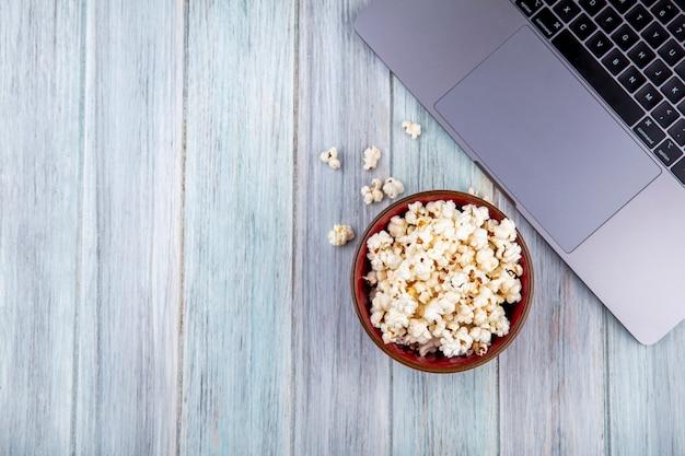 Bovenaanzicht van smakelijke popcorn op een houten kom op grijze houten oppervlak