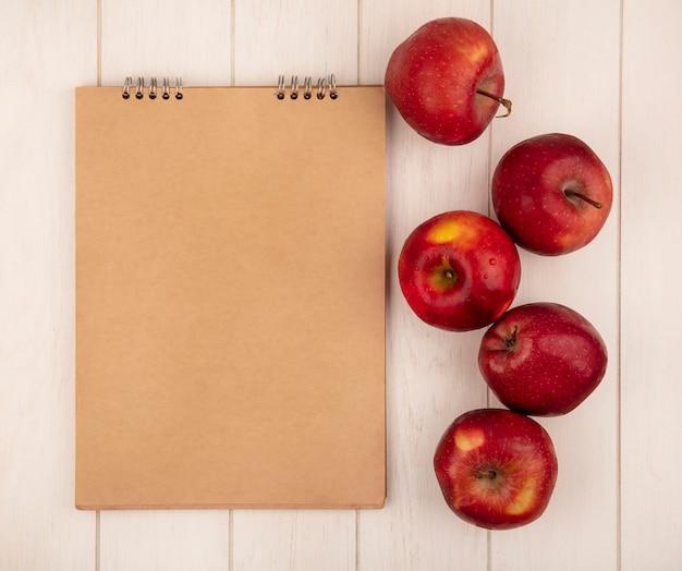 Bovenaanzicht van smakelijke rode appels geïsoleerd op een witte houten oppervlak met kopie ruimte